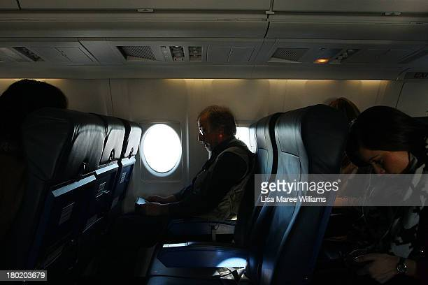Members of the Australian media work during a flight from Melbourne to Townsville on the press plane on August 30 2013 in Melbourne Australia...