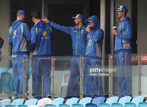 Members of the Australian team are seen as rain delays play on day two of the Second Test match between Australia and South Africa at Blundstone...