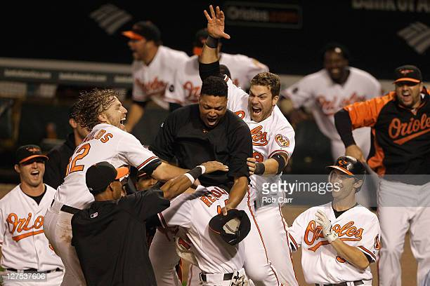 Members of the Baltimore Orioles swarm Nolan Reimold after he scored the winning run to defeat the Boston Red Sox 43 at Oriole Park at Camden Yards...