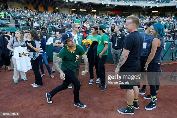 Members of the band Green Day stand on the field prior to the game between the Seattle Mariners and the Oakland Athletics at Oco Coliseum on...