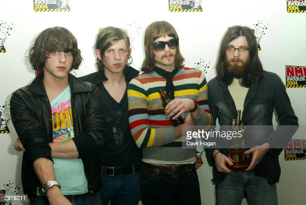 Members of the band Kings of Leon stand together with the award for Best New Band while in the pressroom for the NME Awards 2004 on February 12 2004...