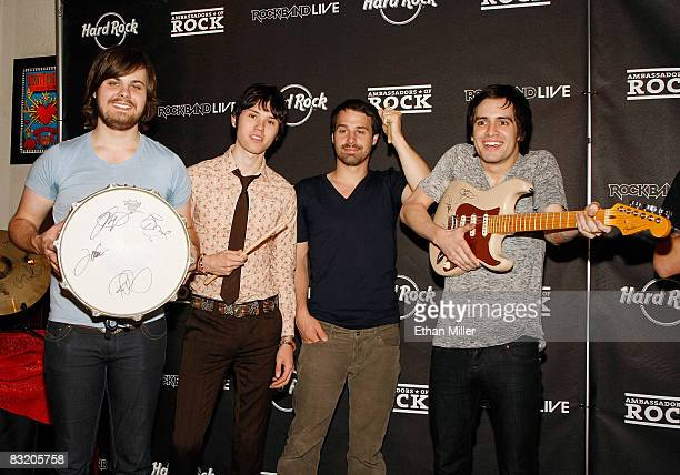 Members of the band Panic at the Disco drummer Spencer Smith guitarist Ryan Ross bassist Jon Walker and frontman Brendon Urie pose with memorabilia...