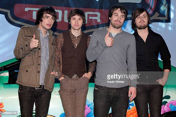Members of the band Panic at the Disco frontman Brendon Urie guitarist Ryan Ross bassist Jon Walker and drummer Spencer Smith pose onstage during the...