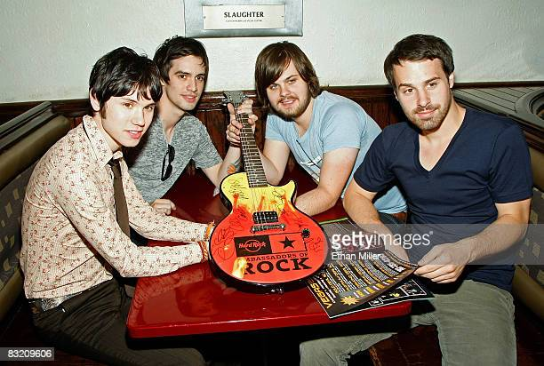 Members of the band Panic at the Disco guitarist Ryan Ross frontman Brendon Urie drummer Spencer Smith and bassist Jon Walker pose with an...