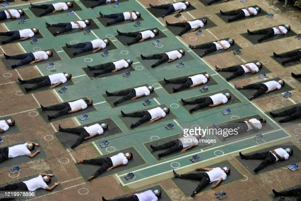 Members of the Bangladesh police wearing face masks attend a yoga sessionto boost their immune system during the COVID-19 coronavirus pandemic in...
