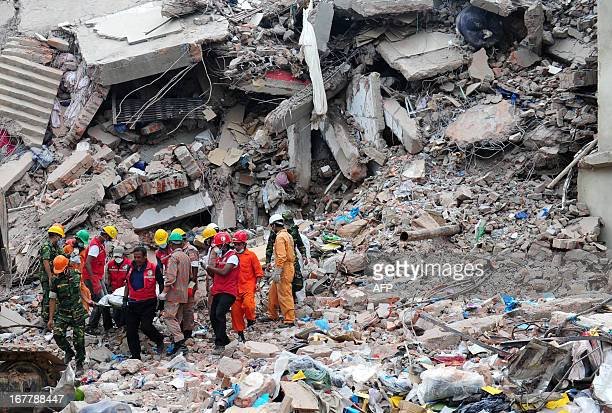 Members of the Bangladeshi Army carry the body of a garment worker as heavy equipment is brought in to remove debris following an eightstorey...