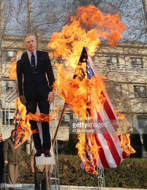 Members of the Basij a militia loyal to the Islamic republic's establishment burn a cardboard cutout of Britain's ambassador Rob Macaire along a...