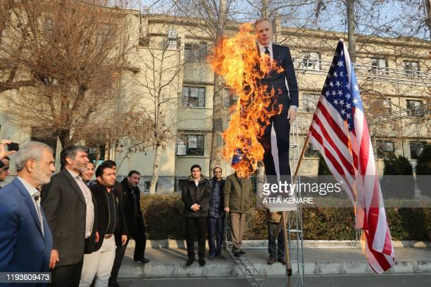Members of the Basij, a militia loyal to the Islamic republic's establishment, burn a cardboard cutout of Britain's ambassador Rob Macaire along a...