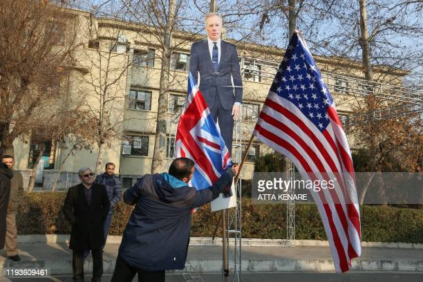 Members of the Basij a militia loyal to the Islamic republic's establishment prepare to burn a cardboard cutout of Britain's ambassador Rob Macaire...