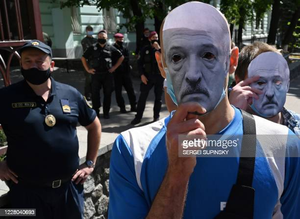 Members of the Belarusian diaspora and Ukrainian activists hold masks depicting Belarusian President Alexander Lukashenko during a rally in support...