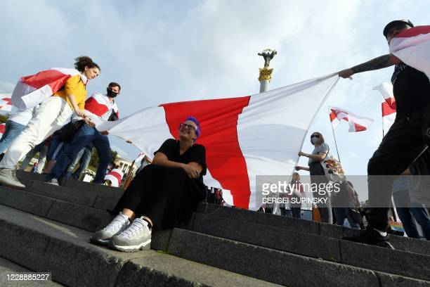 Members of the Belarusian diaspora carry a giant former Belarus white-red-white flag on October 4, 2020 during a rally on Independence Square in Kiev...