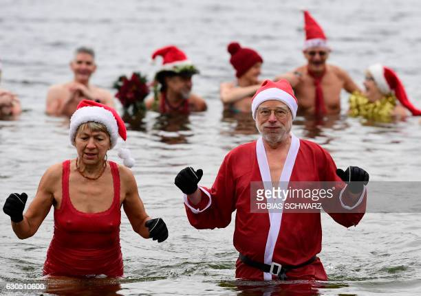 Members of the Berliner Seehunde swimming club with Father Christmas outfits pose for a picture during their traditional Christmas swimming on...