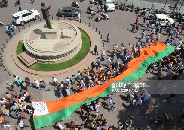 Members of the Bharatiya Janata Party carry a BJP giant flag during a march to pay tribute to Indian socialist revolutionary Bhagat Singh near...