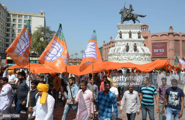 Members of the Bharatiya Janata Party carry BJP flags during a march to pay tribute to Indian socialist revolutionary Bhagat Singh near Jallianwala...