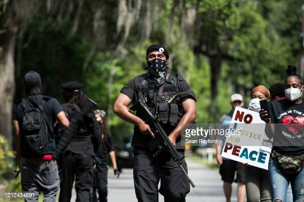 "Members of the Black Panther Party, ""I Fight For My People"", and ""My Vote is Hip Hop"" demonstrate in the Satilla Shores neighborhood on May 9, 2020..."