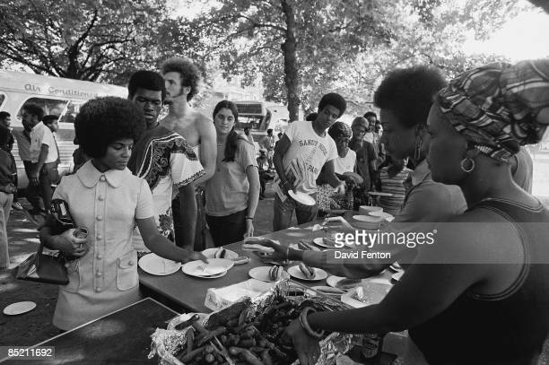 Members of the Black Panther Party stand behind tables and distribute free hot dogs to the public, New Haven, Connecticut, late 1960s or early 1970s.