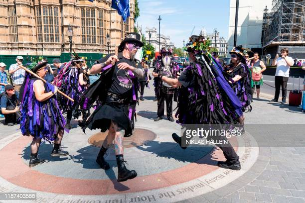 Members of the Black Swan Border Morris dancing team take part in a demonstration by morris dancing teams in Parliament Square in London on July 23...