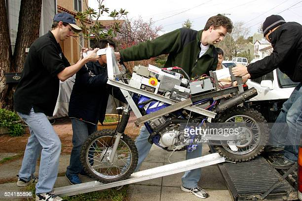 Anthony Levandowski Ognen Stojanovski and Frank Wang roll the vehicle out of the garage to test their robotic motorcycle in preparation of the DARPA...