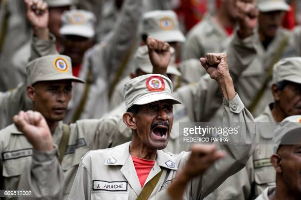 TOPSHOT Members of the Bolivarian Militia take part in a parade in the framework of the seventh anniversary of the force in front of the Miraflores...