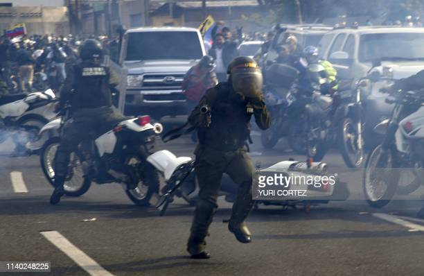 TOPSHOT Members of the Bolivarian National Guard loyal to Venezuelan President Nicolas Maduro run under a cloud of tear gas after being repelled by...