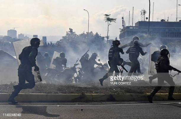 Members of the Bolivarian National Guard loyal to Venezuelan President Nicolas Maduro run under a cloud of tear gas after being repelled with rifle...