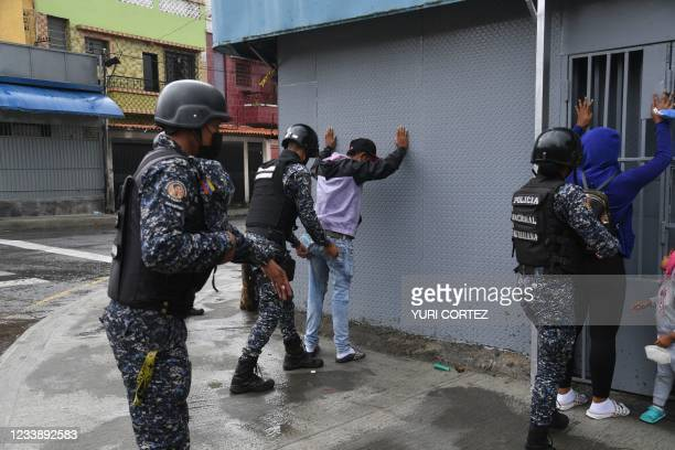 Members of the Bolivarian National Police frisk people during clashes with alleged members of a criminal gang in the surroundings of La Cota 905...