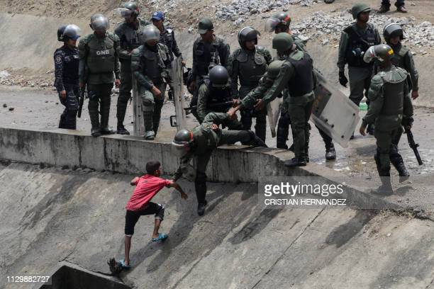 Members of the Boliviarian Guard prevent a child from collecting water from a broken pipe flowing into a sewage canal at the Guaire river in Caracas...