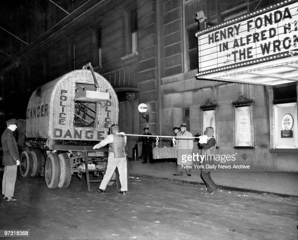 Members of the bomb squad haul a mesh iron sealer containing a bomb from the Paramount theater's side entrance to the truck which will go to Fort...
