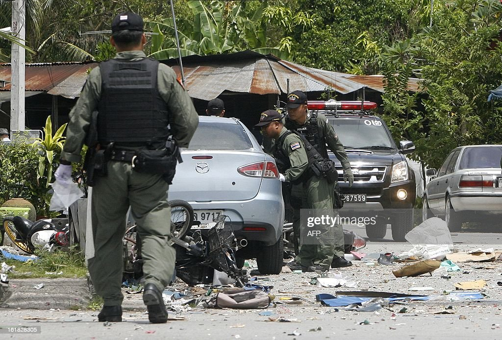 Members of the bomb squad inspects the site of bomb blast, detonated by suspected separatist militants at the clock tower intersection in Pattani town on February 17, 2013. A shadowy insurgency calling for greater autonomy has plagued Thailand's far south near the border with Malaysia since 2004, claiming more than 5,300 lives, both Buddhist and Muslim. AFP PHOTO/Tuwaedaniya MERINGING
