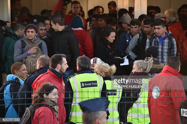 Members of the border force stand guard as unaccompanied migrant minors living near the demolished 'Jungle' migrant camp in Calais wait to leave for...