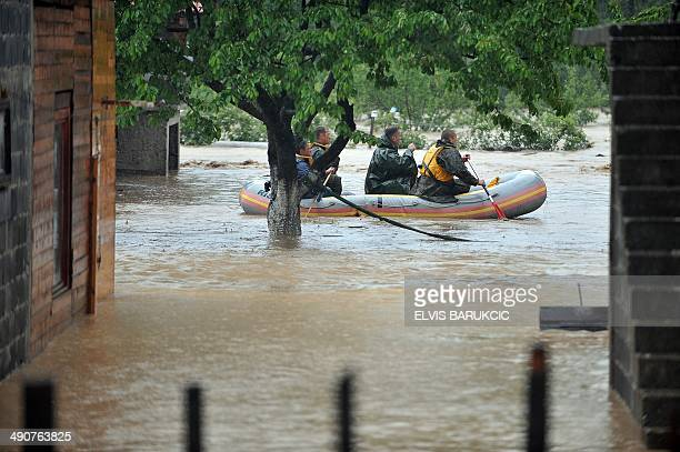 Members of the Bosnian armed forces use an inflattable boat during an operation to evacuate residents from homes surrounded by flood waters in the...