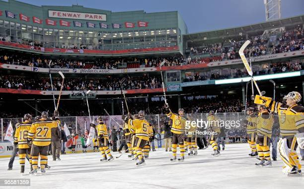 Members of the Boston Bruins raise their sticks to salute the fans after defeating the Philadelphia Flyers 21 in overtime on January 1 2010 during...