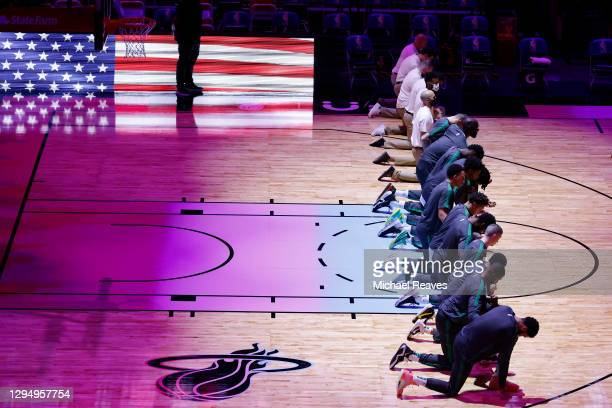 Members of the Boston Celtics kneel during the playing of the national anthem prior to the game against the Miami Heat at American Airlines Arena on...