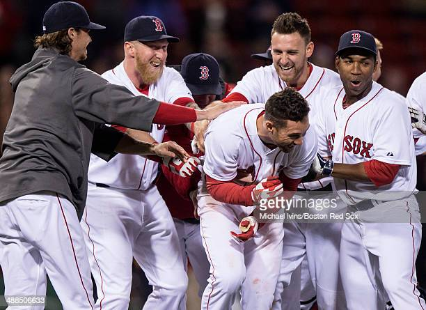 Members of the Boston Red Sox celebrate after an RBI hit by Grady Sizemore won the game against the Cincinnati Reds in the eleventh inning at Fenway...