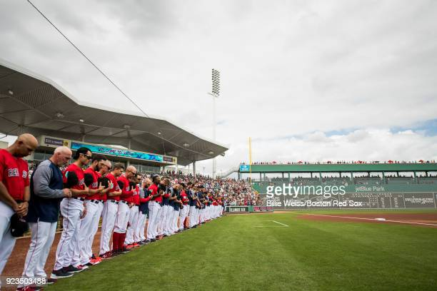 Members of the Boston Red Sox wear the hat of the Marjory Stoneman Douglas High School Eagles baseball team and observe a moment of silence during a...