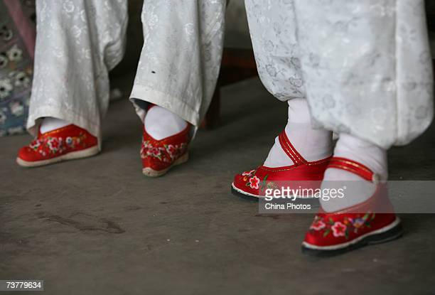 Members of the Bound Feet Women Dancing Team dance on their Three Cuns Golden Lotus shoes at Liuyi Village on April 2 2007 in Tonghai County of...