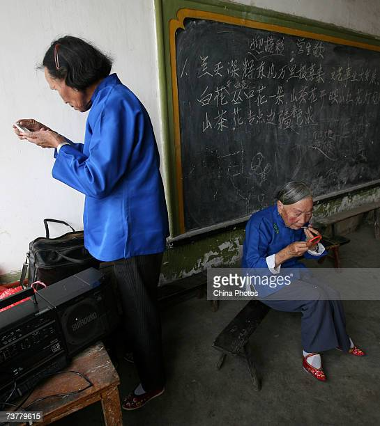 Members of the Bound Feet Women Dancing Team put on their makeup before dancing practice at Liuyi Village on April 2 2007 in Tonghai County of Yunnan...