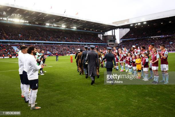 Members of the British Armed Forces walk out on the pitch as part of a ceremony for Remembrance Day prior to the Premier League match between Aston...