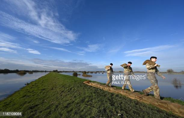 Members of the British Army carry sandbags as they work to create a blockade along the bank of the River Don after it flooded a field in Stainforth...