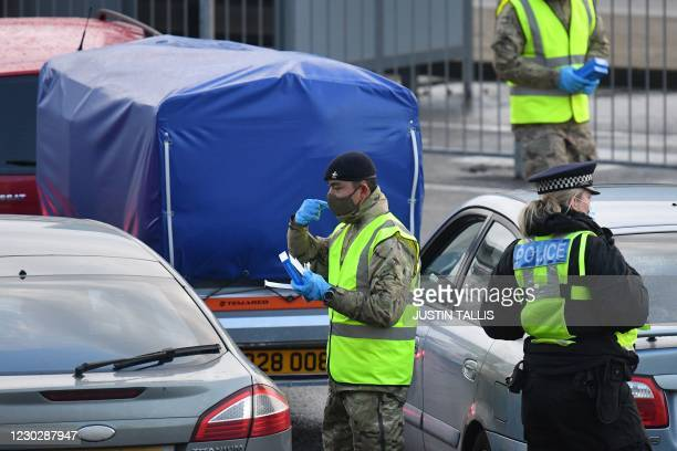 Members of the British army help travellers to use covid-19 self-testing kits close to the entrance to the Port of Dover, in Dover on the south-east...