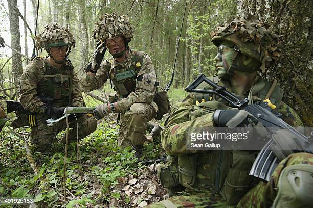 Members of the British Duke of Lancaster's Regiment plan their movements against the enemy while a member of the Estonian Scouts Battalion looks on...