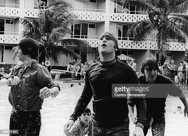 Members of the British pop group the Beatles climb out of a pool during filming of a movie tentatively called 'Beatles 2' Nassau Bahamas February 26...
