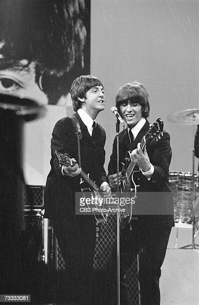 Members of the British rock band The Beatles, Paul McCartney and George Harrison , sing into a microphone as they play their instruments at the...