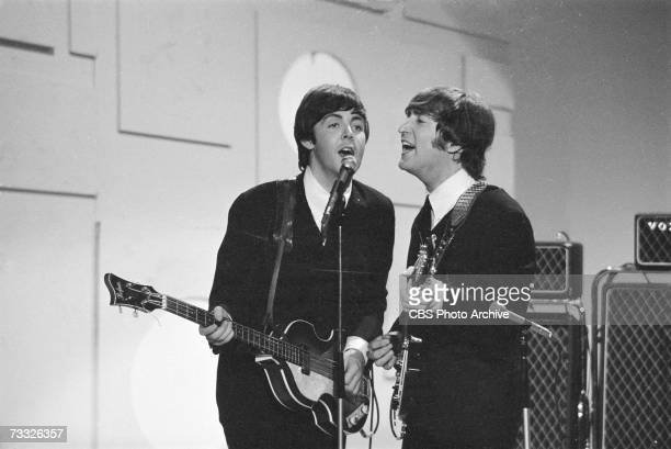 Members of the British rock band The Beatles Paul McCartney and John Lennon sing into a microphone as they play their instruments at the taping of a...