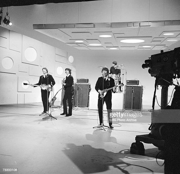 Members of the British rock band The Beatles, Paul McCartney, George Harrison , Ringo Starr, and John Lennon , sing into microphones as they play...