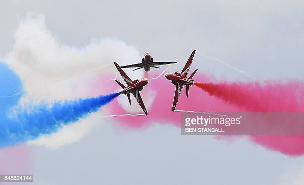 Members of the British Royal Air Force Aerobatic Team the Red Arrows perform ahead of the British Formula One Grand Prix at Silverstone motor racing...