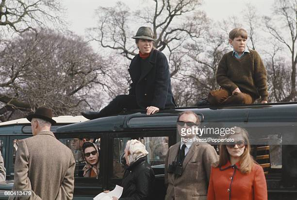 Members of the British royal family, including Queen Elizabeth II seated inside a Land Rover Series IIA station wagon with Princess Anne and Prince...