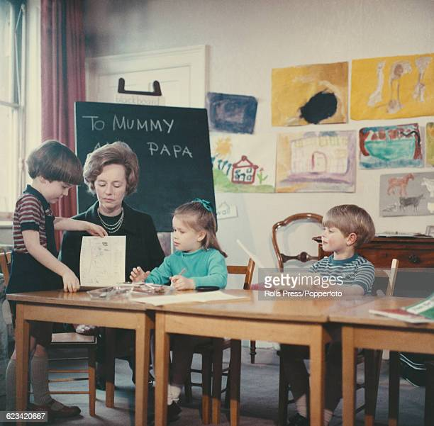Members of the British Royal Family Lady Sarah ArmstrongJones and Prince Edward pictured together with a teacher and fellow pupil at nursery school...