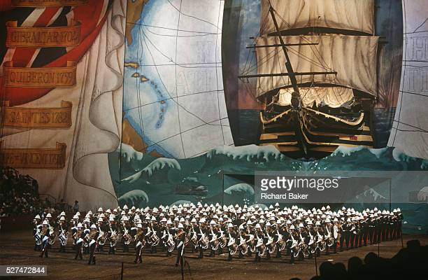 Members of the British Royal Marines band march under a giant backdrop of Lord Horatio Nelson's flagship HMS Victory during the Royal Tournament...