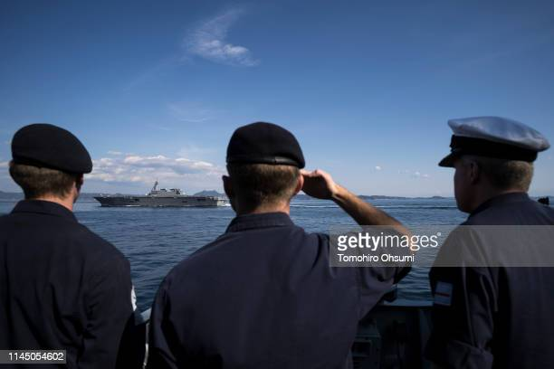 Members of the British Royal Navy look at Japanese Maritime SelfDefense Force's Izumo helicopter carrier on board the HMS Montrose frigate as it...